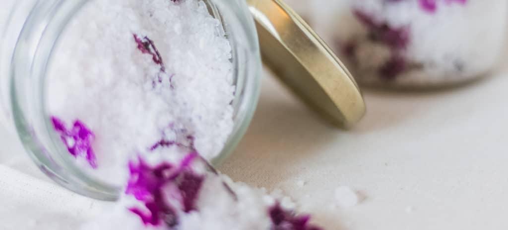 open jar of white bath salt with magenta flowers