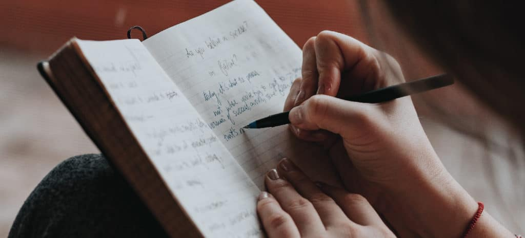 person writing in notebook