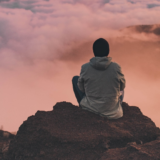 person sitting on high rock looking out at clouds