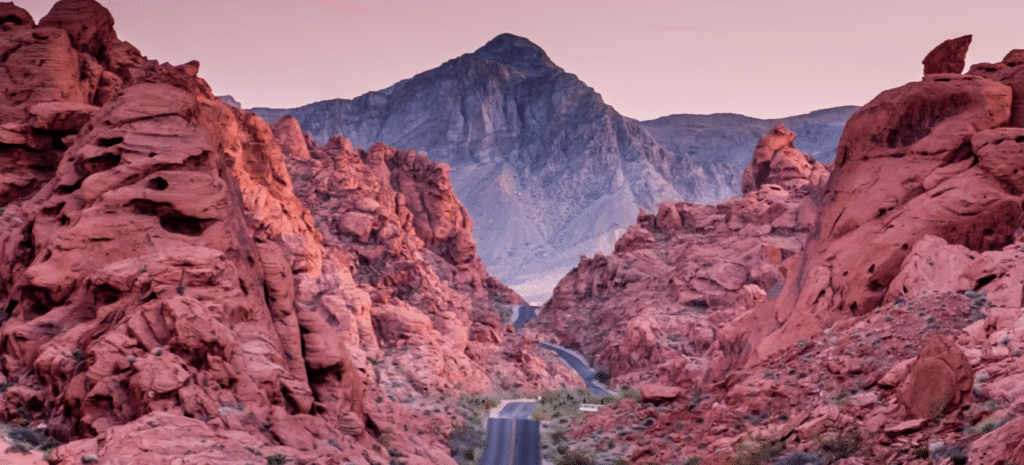 road through rocks with mountain backdrop