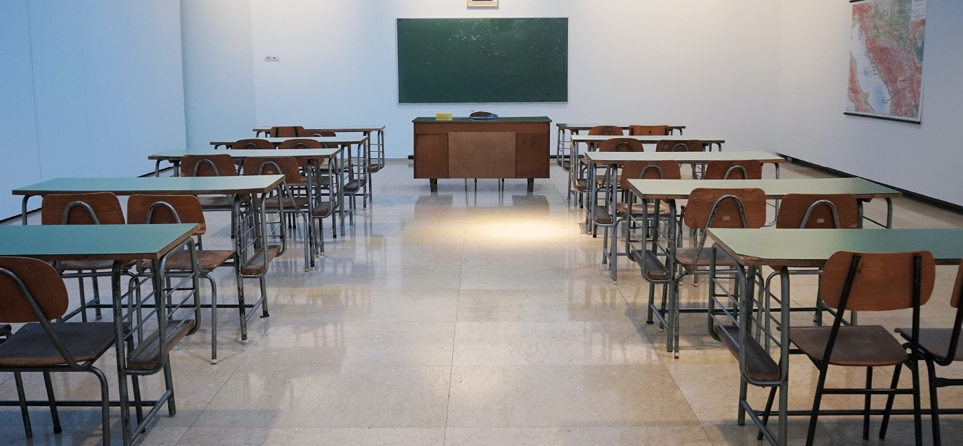 classroom with desks chairs and blackboard