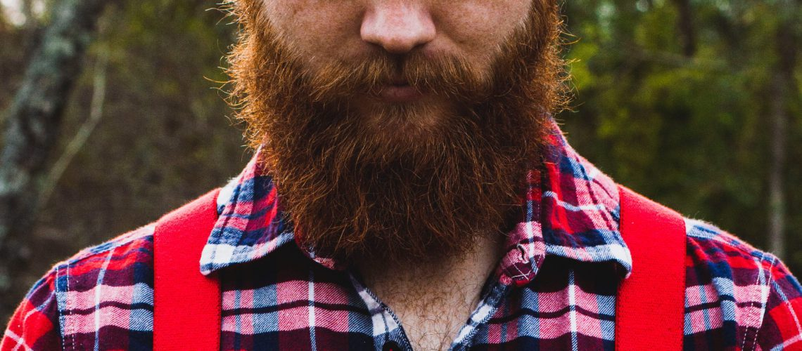 beard shot of man wearing red plaid and overalls